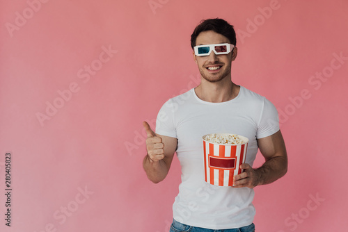 Fotografie, Obraz front view of smiling muscular man in 3d glasses holding popcorn and showing thu