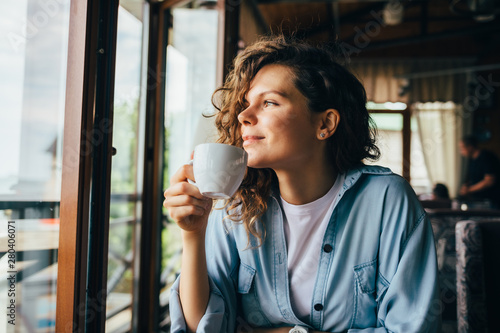 Obraz Smiling calm young woman drinking coffee - fototapety do salonu