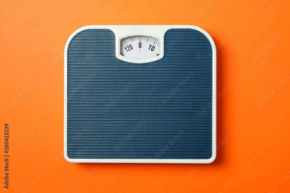 Fototapety, obrazy: Blue weigh scales on orange background, top view