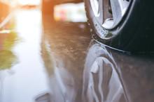 Car Tire Splashing In Water, Modern Rain Summer Season Tires On The Wet Pavement. Closeup Aquaplaning Photo.