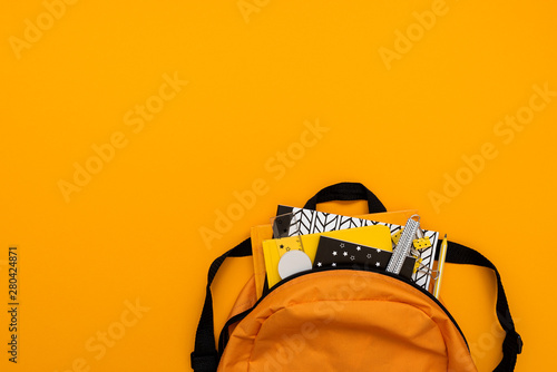 Obraz Back to school concept. Backpack with school supplies on yellow background. Top view. Copy space. Flat lay - fototapety do salonu