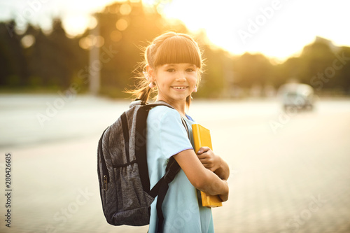 Happy little student girl with a backpack on her way to school. Fototapete