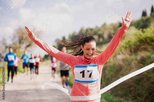 canvas print motiv - Halfpoint : Young woman runner crossing finish line in a race competition in nature.