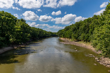 Water Flowing Along Rocky Riverbank Of Sangamon River Surrounded By Trees On A Sunny Day With Clouds