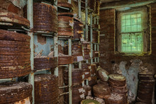 Destroyed From Time To Time Storage Room With Stored Old Rusty Round Boxes With Old Film