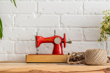 Red Sewing Machine On A Wooden...