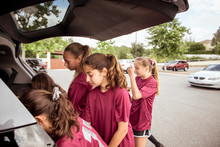 Female Soccer Players Unloading Car While Standing On Road