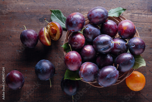 Ripe juicy plums on a wooden background. Canvas Print