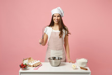 Housewife Female Chef Cook Confectioner Or Baker In Apron White T-shirt, Toque Chefs Hat Cooking Cake Or Cupcake At Table Isolated On Pink Pastel Background In Studio. Mock Up Copy Space Food Concept.