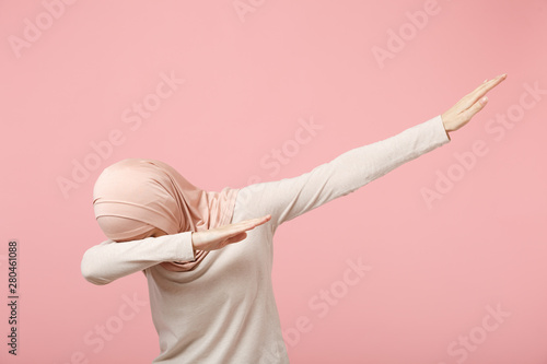 Cuadros en Lienzo  Young arabian muslim woman in hijab light clothes posing isolated on pink wall background studio portrait