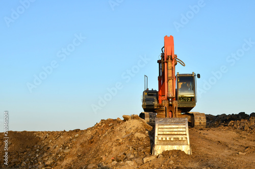 Excavator at a construction site during earthworks and laying of underground pipes Tapéta, Fotótapéta