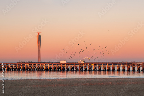 Sunset on the old wooden pier of Ostend, with modern radar tower in the background. Lots of seagulls flying around.