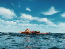 Full Body Portrait Of Female Surfer Lying On Surfboard
