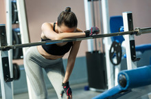 Exhausted Girl In A  Gym Taking A Break Leaning On A Barbell.