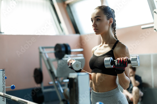 Fotografia  Young sporty woman exersises biceps with dumbells in a gym