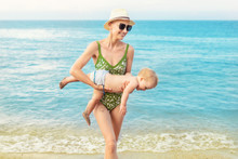 Young Beautiful Bald Mother Carrying Cute Caucasian Toddler Boy Out Clear Blue Water At Tropical Beach With Warm Summer Rain. Mom Having Fun With Baby Son At Sea Or Ocean. Travel Vacation And Holiday