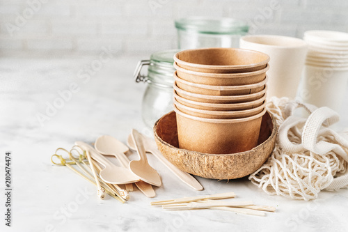 Valokuva  Eco tableware. Paper and bamboo cups, bag and wooden cutlery.