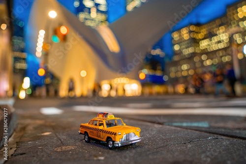 Tuinposter New York TAXI Vintage old Taxi toy in New York City most popular places. Classic Yellow Cab in Manhattan and Brooklyn. The symbol of New York. Driving a taxi through Manhattan island.