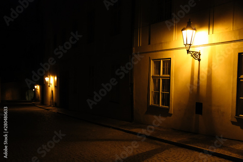 Fotografie, Obraz  Old lanterns illuminating a dark alleyway medieval street at night in Prague, Czech Republic