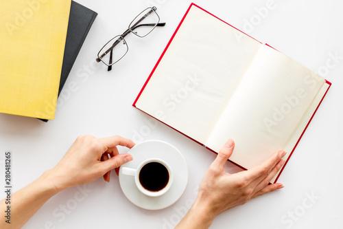Fotografija  Book in hands cover near glasses, coffee on white desk background top view mock