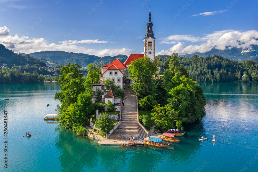 Fototapety, obrazy: Bled, Slovenia - Aerial view of beautiful Pilgrimage Church of the Assumption of Maria on a small island at Lake Bled (Blejsko Jezero) and lots of Pletna boats on the lake at summer time with blue sky