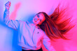 Leinwanddruck Bild portrait of young elegant girl. Colored neon background, studio shot. Beautiful brunette woman. Hipster girl dancing in neon. Woman with stylish hair and red lips. Girl in a sweater and long hair.