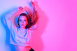 Leinwanddruck Bild Fashion portrait of young elegant girl.Colored neon background, studio shot. Beautiful brunette woman. Hipster girl dancing in neon. Woman with stylish hair and red lips. Girl in a sweater