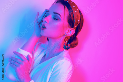 Leinwanddruck Bild - MoreThanProd : Fashion portrait of young elegant girl in a white dress. Sensual beautiful brunette, long hair. Leopard print accessories. Woman in the earrings and headband. Colored neon background, studio shot.