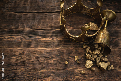 Golden crown and a award cup with a gold on a brown wooden table background with copy space Wallpaper Mural