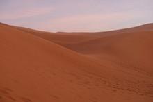 Brown Wide Sahara Desert Sand Dune Slope At Sunset Evening. Pink Cloud Sky Background. Saharan, Sandy Near Merzouga In Morocco