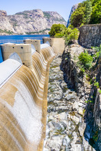 Water Flowing Through The O'Shaughnessy Dam Spillway Due To High Water Levels In The Hetch Hetchy Reservoir, Yosemite National Park, Sierra Mountains, California