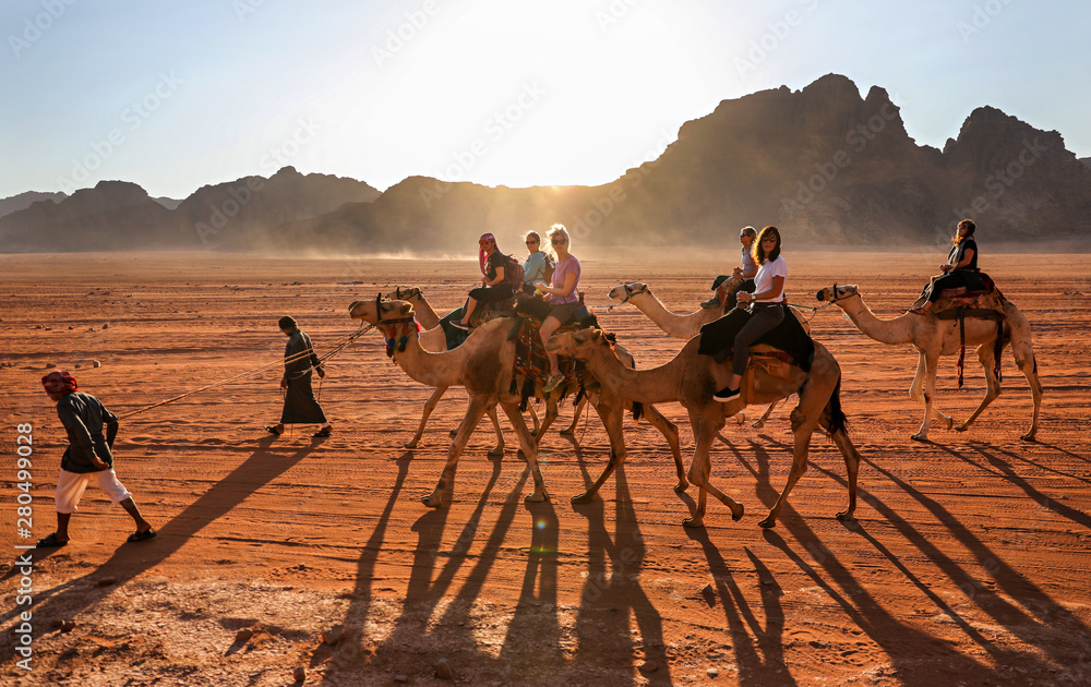 Fototapety, obrazy: Women riding through the desert in Wadi Rum, Jordan, on camels lead by Bedouin guides.