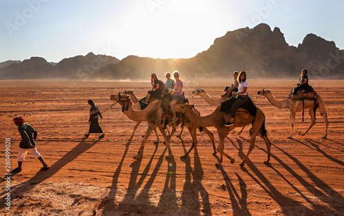 Women riding through the desert in Wadi Rum, Jordan, on camels lead by Bedouin guides.