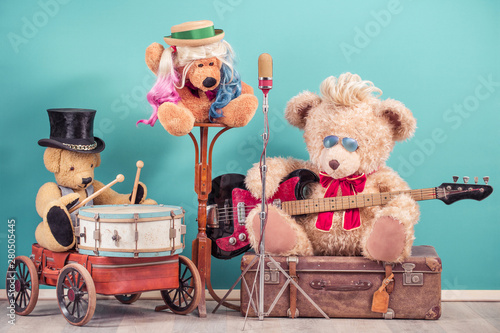 Fotografie, Obraz  Retro Teddy Bear toys with play bass guitar on old luggage, vocalist near golden microphone, bear in cylinder hat playing the drum