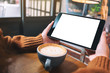 Leinwandbild Motiv Mockup image of hands holding black tablet pc with blank white screen with coffee cup on wooden table