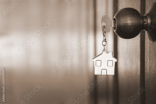 Fotografija Home key with house keyring in keyhole on wooden door