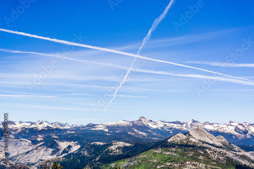 Photo Multiple contrails cross paths through the blue sky above snow capped mountains;