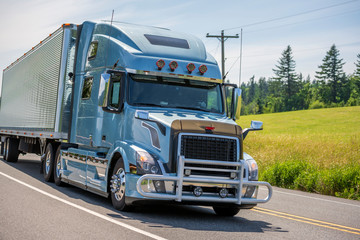 Big rig blue semi truck with grille guard transporting cargo in grooved semi trailer driving on the summer road
