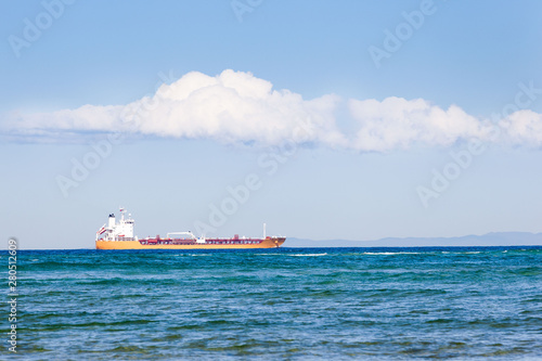 A bright yellow bulk tanker contrasts with the surrounding blue of sea and sky, as it carries its load from one port to another.