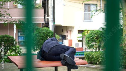 Valokuva ベンチで寝る男性