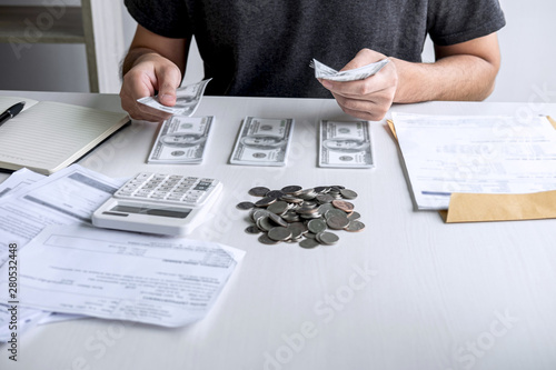 Fotografie, Obraz  Images of stacking coin pile and Husband using calculator to calculating expendi