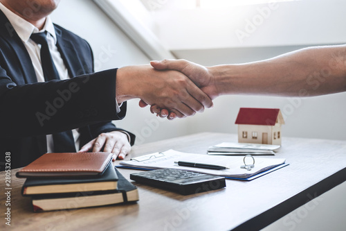 Fototapeta Finishing to successful deal of real estate, Broker and client shaking hands after signing contract approved application form, concerning mortgage loan offer for and house insurance obraz