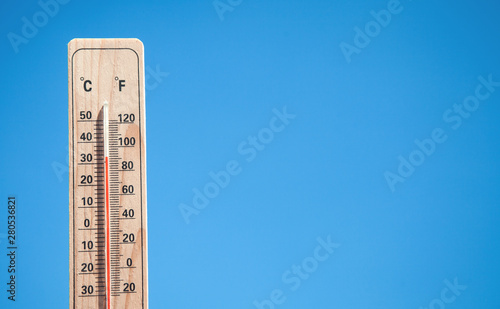 Thermometer on blue sky background.