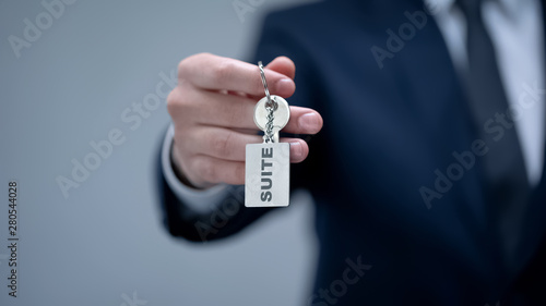 Suite word on keychain in businessman hand, rental premium quality accommodation