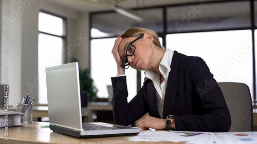 Sad woman looking at laptop, worried about difficult project, lack of experience