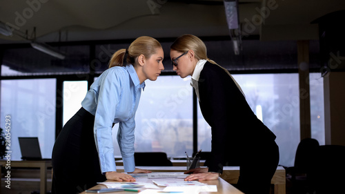 Two businesswomen looking with challenge at each other, competition at work Wallpaper Mural