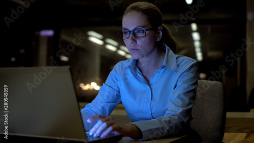 Fotografía  Beautiful woman working on laptop late night in office, conscientious employee