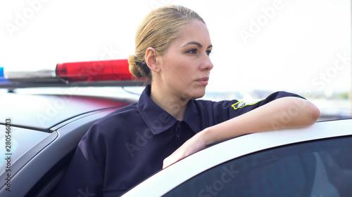 Obraz na plátně Brave policewoman standing near patrol car, protection of public order in city