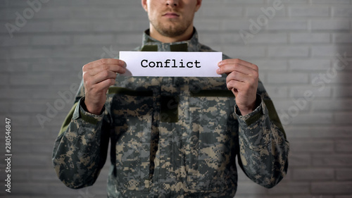 Conflict word written on sign in hands of soldier, military annexation, war Canvas Print