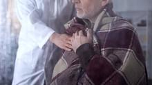 Female Nurse Covering Male Pat...